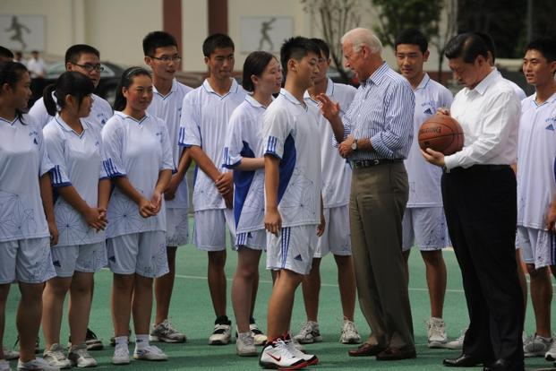 Xi signs a basketball at Dujiangyan Qingchengshan high school outside Chengdu in China's southwest province of Sichuan on 21 August 2011 even as US Vice President Joe Biden (centre) talks with a student. AFP