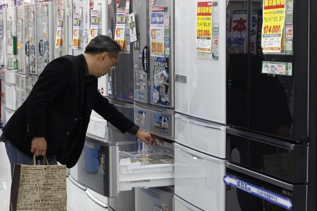A man looks at a Hitachi refrigerator at an electronics shop in Tokyo. Hitachi's consumer products division accounted for 8.3% of sales in the quarter ended September, down from 12% four years ago. Photo: Reuters