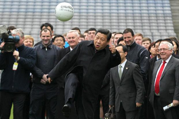 China's new party supremo Xi Jinping (centre) kicks a football as he visits Croke Park in Dublin, Ireland on 19 February 2012. He is the son of Xi Zhongxun, a Communist revolutionary hero and former vice premier. AFP