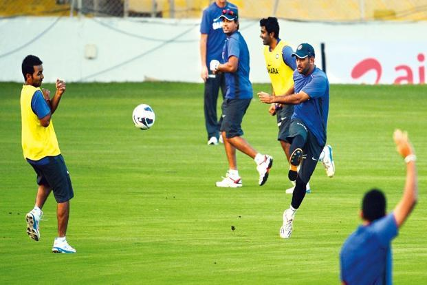 Indian captain M.S. Dhoni (right) playing football with teammates during a training session. Photo: Punit Paranjpe /AFP