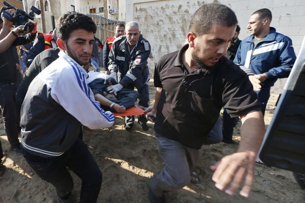 Palestinians take away a wounded man after an Israeli air strike took place near his car in the northern Gaza Strip on Thursday. Photo: Mohammed Salem/Reuters