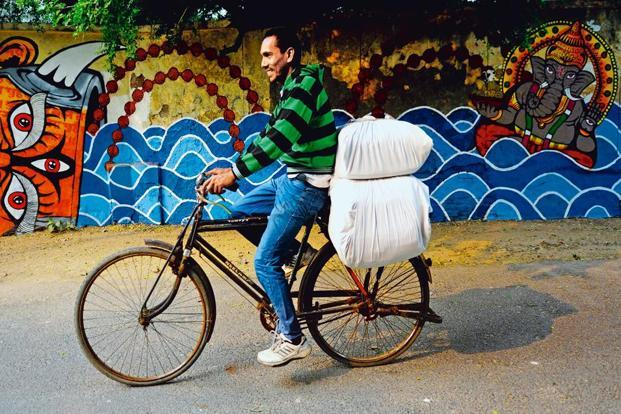 Chandrapal cycles out of Hailey Lane, on his way to deliver laundered clothes.