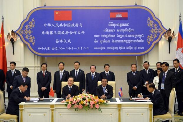 Chinese commerce minister Chen Deming (left) signs an agreement with Cambodian deputy prime minister and finance minister Keat Chhon (right) as Chinese Premier Wen Jiabao (centre-left) and Cambodian Prime Minister Hun Sen (centre-right) look on at the Peace Palace in Phnom Penh, ahead of the 21st Asean summit. Photo: Tang Chhin Sothy/AFP