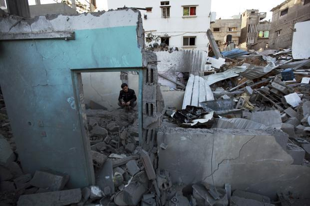 A Palestinian man sits amongst the rubble of a destroyed house after an Israeli air strike in the northern Gaza Strip on Sunday. Photo: Mohammed Salem/Reuters
