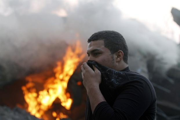 A man covers his face as he passes through smoke and fire after Israeli air strikes in Gaza City. AFP
