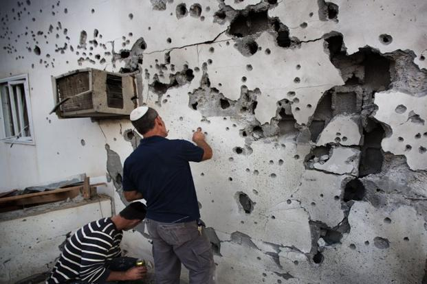 Israeli men inspect the damage caused to a house by a rocket launched by Palestinian militants from the Gaza Strip in the southern Israeli town of Ofakim. AFP