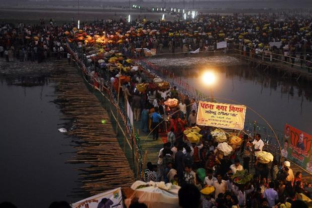 Devotees cross a bamboo bridge as they gather to pay homage to the setting sun during Chhath Puja on the banks of the Ganges river in Patna. Photo: AFP