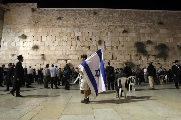 A man holds an Israeli flag during a mass prayer for soldiers and civilians at the Western Wall, Jerusalem, even as Palestinian rocket attacks on Israel and Israeli air strikes on the Gaza Strip continued. Reuters