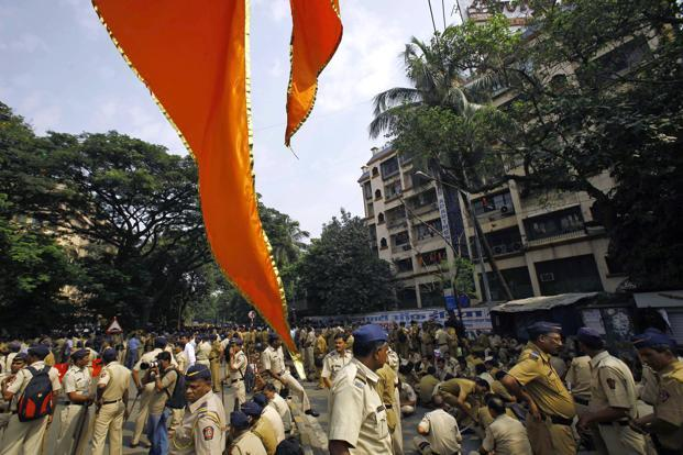 In a file photo, a Shiv Sena flag hangs in the foreground as policemen are deployed outside the residence of Shiv Sena chief Bal Thackeray in Mumbai. Photo: AP