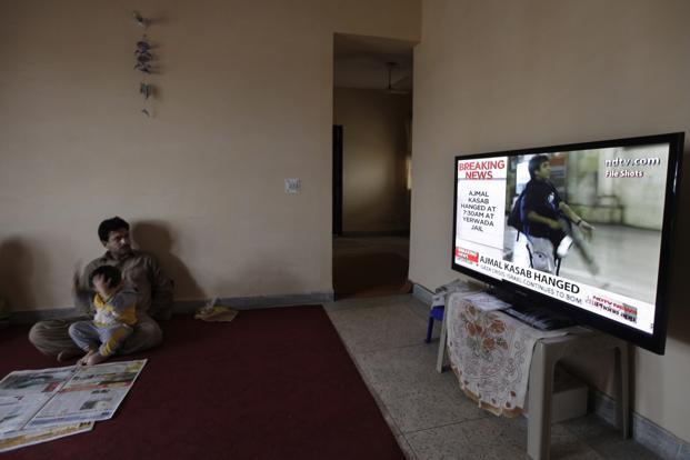 A man watches on television news of India executing Ajmal Kasab. Photo: Altaf Qadri/AP