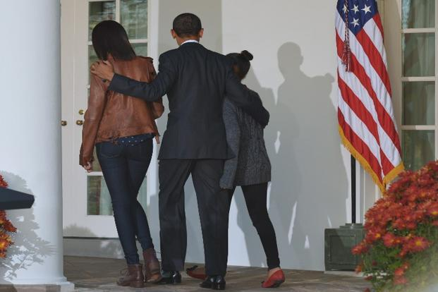 US President Barack Obama walks away with daughters Malia and Sasha after the annual Thanksgiving turkey pardon. AFP
