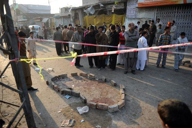 Local residents gather at the site of an overnight suicide bomb attack on minority Shiite Muslims procession in Rawalpindi. Photo: Aamir Qureshi/AFP