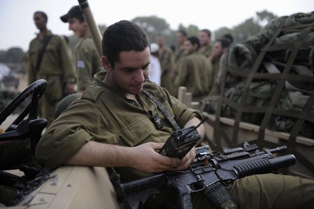 An Israeli soldier checks his radio while relaxing as troops prepare to leave a deployment area near the Israel-Gaza Strip border on Thursday. Photo:AFP
