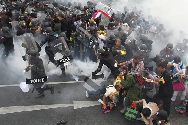 Tear gas is thrown as police scuffle with anti-government protesters near the government house in Bangkok on Saturday. Photo: Reuters