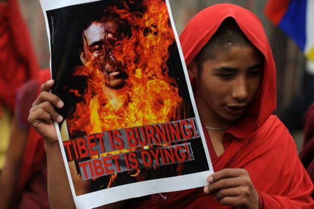 A file photo of a Tibetan monk holding a poster depicting a burning monk during a rally in Siliguri. Photo: Diptendu Dutta/AFP