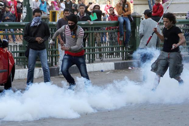 An Egyptian protester kicks a tear gas canister during clashes with Egyptian riot police in Tahrir square on Sunday in Cairo. Photo: AFP