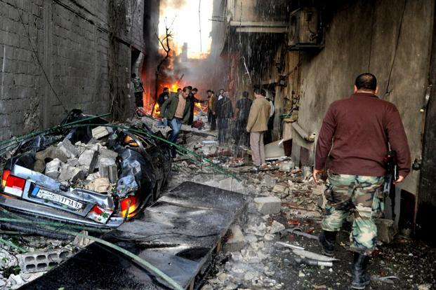 A Syrian soldier (right) and citizens gather at an alley that was destroyed by two cars bombs, at Jaramana neighbourhood, in the suburb of Damascus on Wednesday. Photo: AP