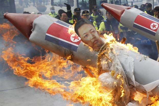 Policemen watch as protesters burn an effigy of North Korean leader Kim Jong-Un bound on a mock North Korean missile. North Korea had said its much hyped long-range rocket launch failed, in a very rare and embarrassing public admission of failure and a blow for its leader who faced international outrage over the attempt. North Korea's state news agency on Saturday announced the decision to launch another space satellite. Photo: Lee Jae-Won/Reuters