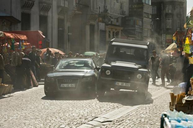 A still from the movie 'Skyfall'. JLR made a comeback in this movie with a Land Rover Defender (right) in the opening scene. Photo: Columbia Pictures