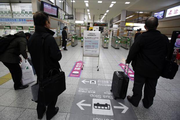 Men stand near a sign alerting passengers to a suspension in bullet train services in northeastern Japan due to an earthquake, at Nagano train station, central Japan. Photo: Yuriko Nakao/Reuters