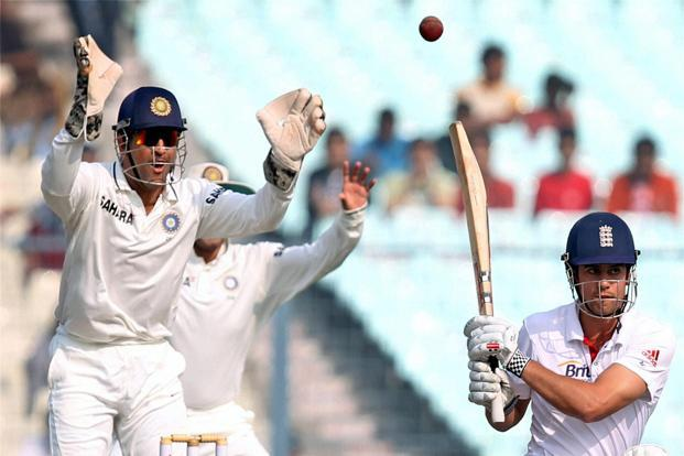 England skipper Alastair Cook plays a shot, with Mahendra Singh Dhoni in the background, during Day 3 of the third cricket test against India at Eden Garden in Kolkata on Friday. Photo: Ashok Bhaumik/PTI