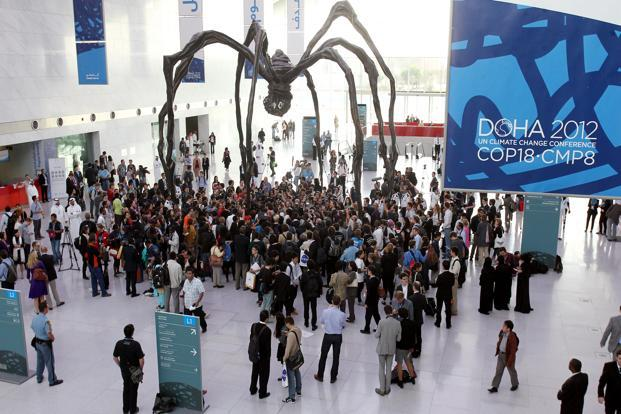 Local and international activists march inside a conference centre under a giant statue of a spider to demand urgent action to address climate change at the UN climate talks in Doha. Photo: AP