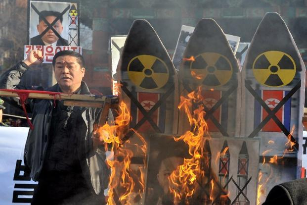 South Korean conservative activists burn anti-North Korean placards during a protest denouncing North Korea's rocket launch, in Seoul. AFP