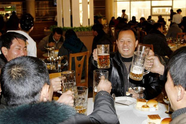 People toast with beer at the newly-built Mansukyo Restaurant in Pyongyang, after hearing news of the country's rocket launch. AP