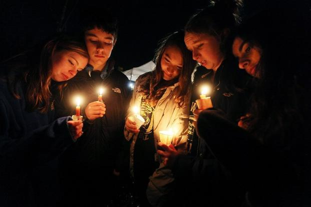 Newtown residents hold candles at a memorial for victims at Sandy Hook Elementary School. AFP
