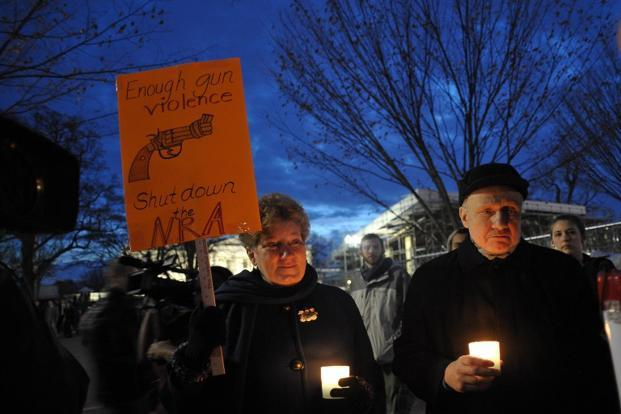 Gun control supporters take part in a candlelight vigil at Lafayette Square across from the White House on 15 December in Washington. The school shooting incident also reignited the perennial debate about gun laws in America. AFP