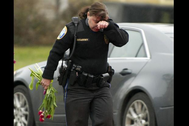 A police officer wipes her eys as she removes flowers from a busy intersection in Newtown, Connecticut, which they said they were afraid the memorial, left for the Sandy Hook Elementary school victims, may cause a traffic hazard. AFP