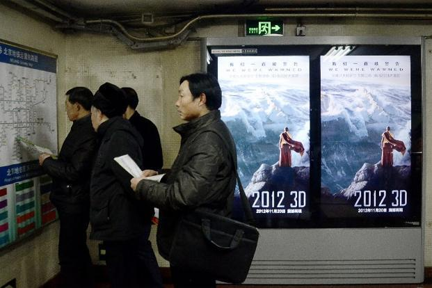 "A group of Chinese men check a map in front of a poster of the movie ""2012"" in Beijing. China had arrested nearly 1,000 people by Thursday, for spreading doomsday rumours and targeting communist rule."