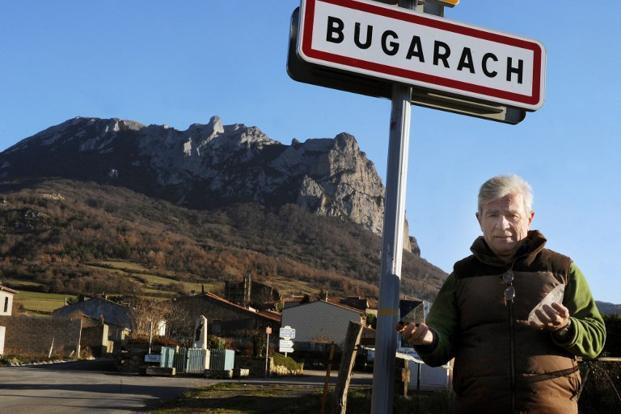 The mayor of Bugarach, Jean-Pierre Delord, poses on 14 December 2010 in front of a Bugarach peak road sign, the 1,231 meter high peak of Bugarah, France. Some doomsday theories say Bugarach peak will be spared on 21 December.