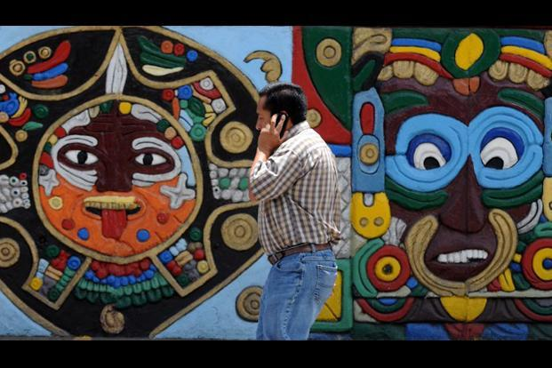 A man walks by a wall displaying Mayan figures in Tegucigalpa.