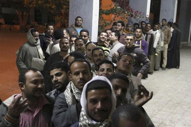 Men queue outside a polling station for voting during the final stage of a referendum on Egypt's new constitution in Bani Sweif, about 115 km south of Cairo on Saturday. Photo: Reuters