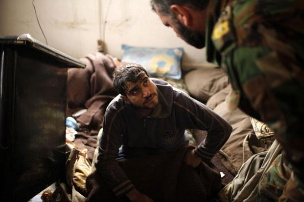 A detainee Syrian soldier loyal to Syria's President Bashar al-Assad is questioned by a Free Syrian Army officer at the army base at Hawa village, north Aleppo, on Sunday. Photo: Ahmed Jadallah/Reuters