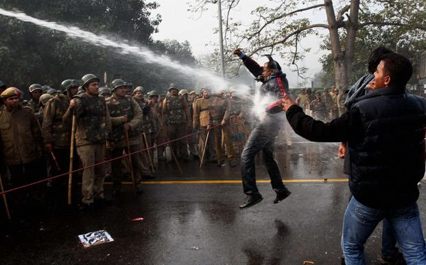 Protesters brave police water cannons during a protest at Rail Bhawan in New Delhi on Sunday. Photo: PTI