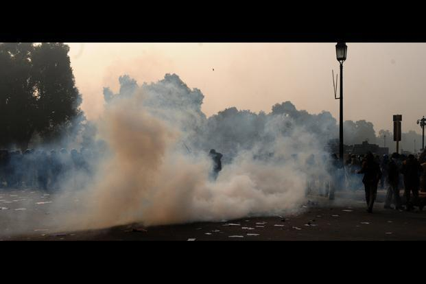 Thick smoke from tear-gas filled the air, forcing the protestors to run helter-skelter. Even media personnel were not spared the wrath of the police.  Ramesh Pathania/Mint