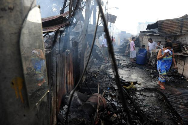 A woman walks amongst destroyed homes after a pre-dawn fire engulfed a slum area in Manila on Tuesday. Photo: AFP
