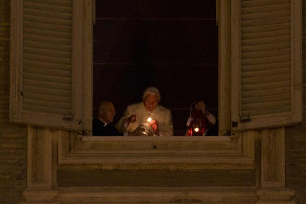 Pope Benedict XVI holds up a candle at the window of his private apartment to celebrate the unveiling of the nativity scene in Saint Peter's Square at the Vatican on Monday. Photo: Reuters