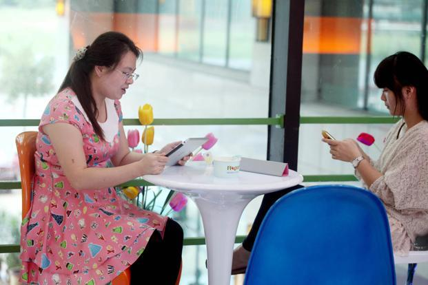 Women use portable devices to browse the Internet in Haikou, in south China's Hainan province. Photo: AFP