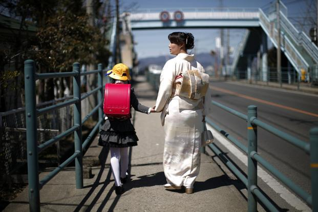 A file photo of a girl walking with her mother in Fukushima in April 2011. Photo: Carlos Barria/Reuters