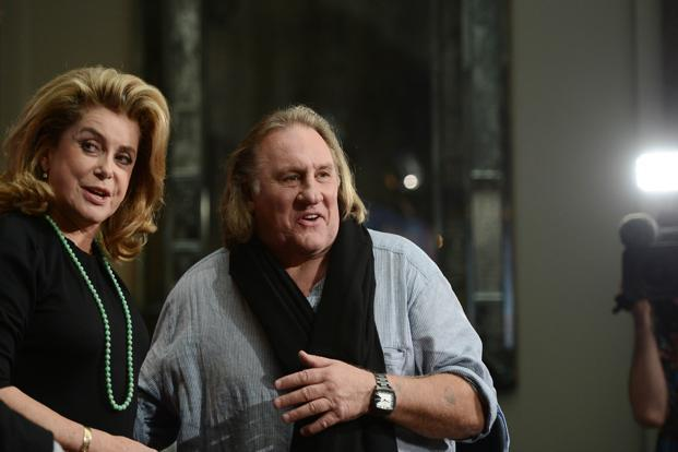 A file photo of French actor Gerard Depardieu, right, and French actress Catherine Deneuve. The proposed tax plan prompted Depardieu to flee abroad. Photo: Johannes Eisele/AFP