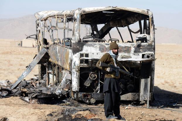 A Pakistani security official beside a destroyed bus at the site of the car bomb attack in Mastung. Photo: Banaras Khan/ AFP