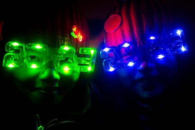 Revellers wear 2013-style glasses as they celebrate the new year      in Beijing. AFP