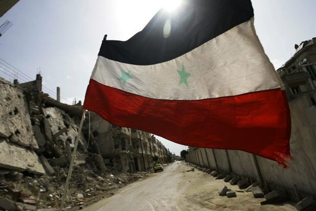 A Syrian flag flutters outside a military barrack in the devastated Baba Amr neighbourhood of Homs, Syria on 2 May 2012. Photos: AFP