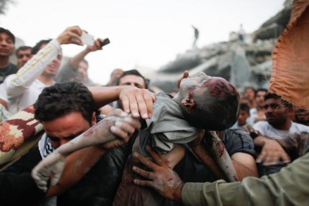 Body of a Syrian child is pulled from rubble after an aerial bombardment from government forces in the Ahad neighbourhood of Aleppo on 11 September 2012.