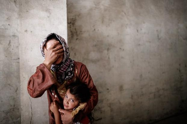 A woman reacts as she holds her daughter during an air strike by Syrian air force near her house in the Ahad neighbourhood of Aleppo on 13 September 2012.