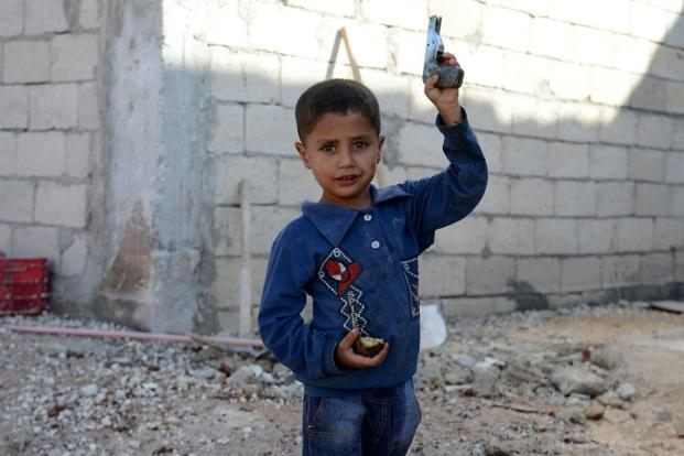 A Syrian boy holds a toy gun in Atareb, Syria.