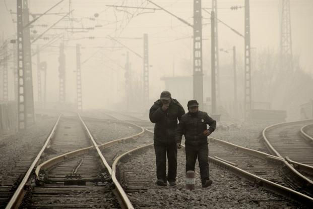 Two men walking along a railway line in Beijing. Commentators say the air pollution illustrates China's persistent challenge to address environmental issues while maintaining its economic growth momentum. AFP